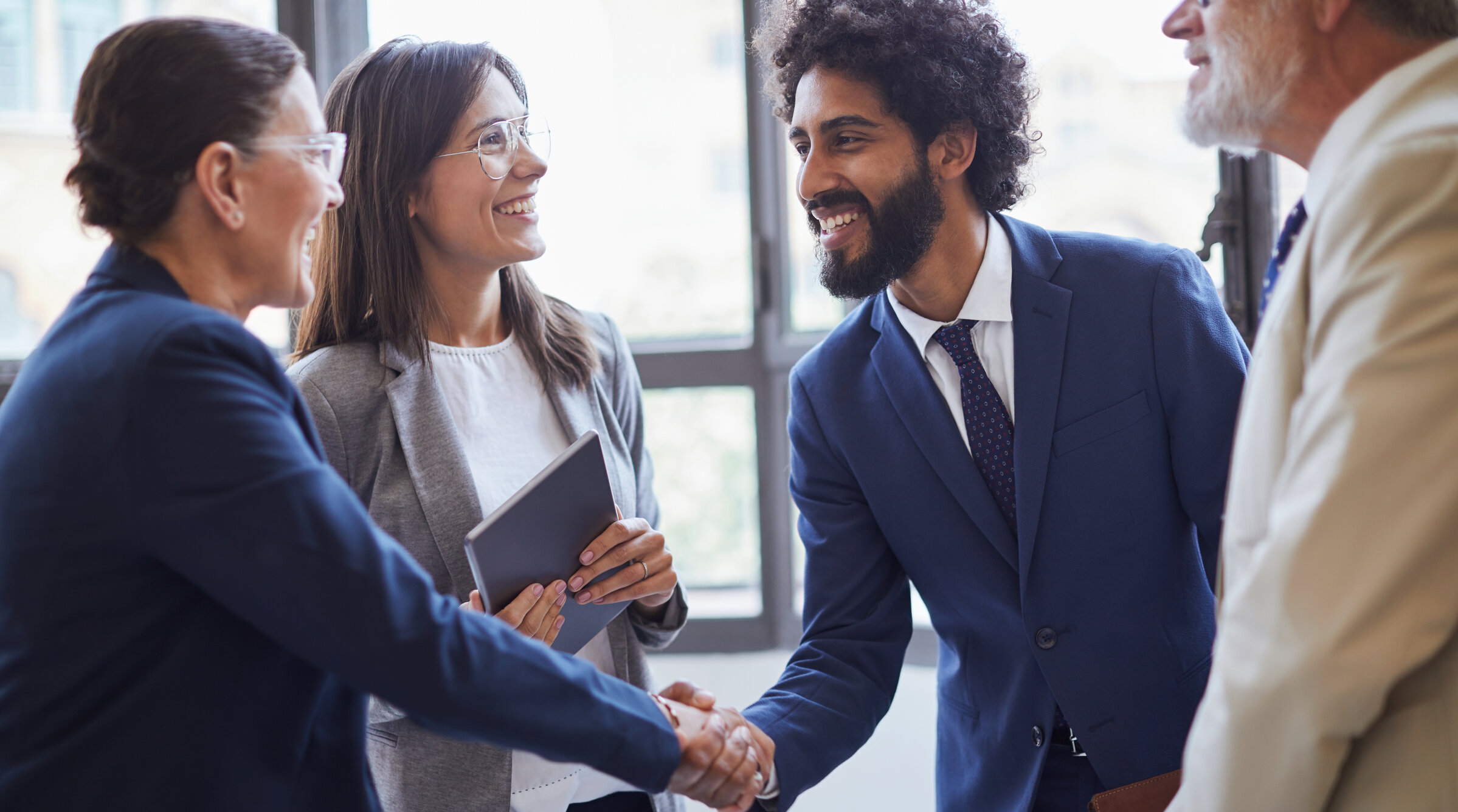 A man and woman shaking hands as part of a group in a business setting.