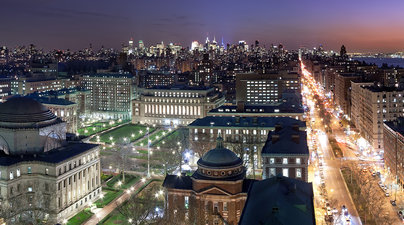 A view of Columbia's campus at night, with the city visible