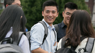Students on campus wearing backpacks and smiling.
