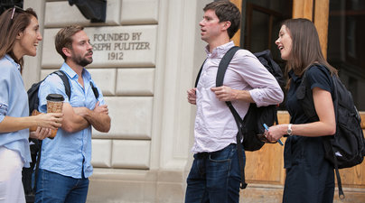 Four students conversing outside Pulitzer Hall.